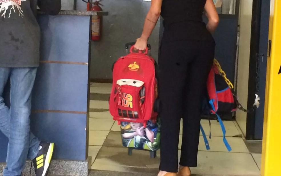Agente leva mochilas das crianças que estavam em van roubada por criminosos (Foto: Bruno Albernaz / G1)
