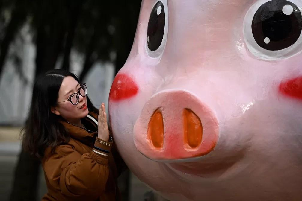 Mulher se aproxima de boneco de porco, símbolo do novo ano chinês, nesta terça-feira (5) em Beijing — Foto: Wang Zhao/ AFP
