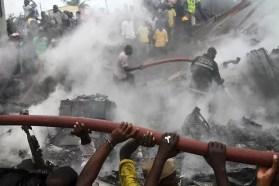 Nigerianos tentam apagar incêndio em local onde ocorreu acidente aéreo, na cidade de Lagos (Foto: Akintunde Akinleye/Reuters)