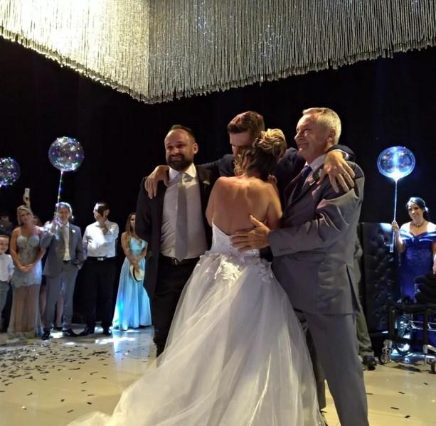 Noivos dançando a valsa com a ajuda do pai de Hugo e de um padrinho — Foto: Cia Sinfônica/ Divulgação