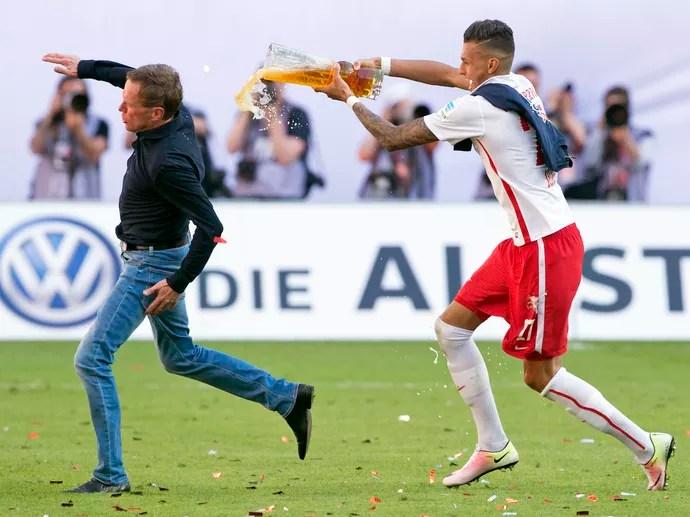 Ralf Rangnick sente dor na coxa ao correr de Davie Selke na comemoração do acesso do Leipzig à Bundesliga (Foto: AP Photo/Jens Meyer)