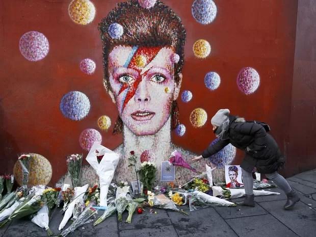 Fã de David Bowie deixa flores em frente ao mural do cantor no bairro de Brixton, em Londres (Foto: Stefan Wermuth/Reuters)