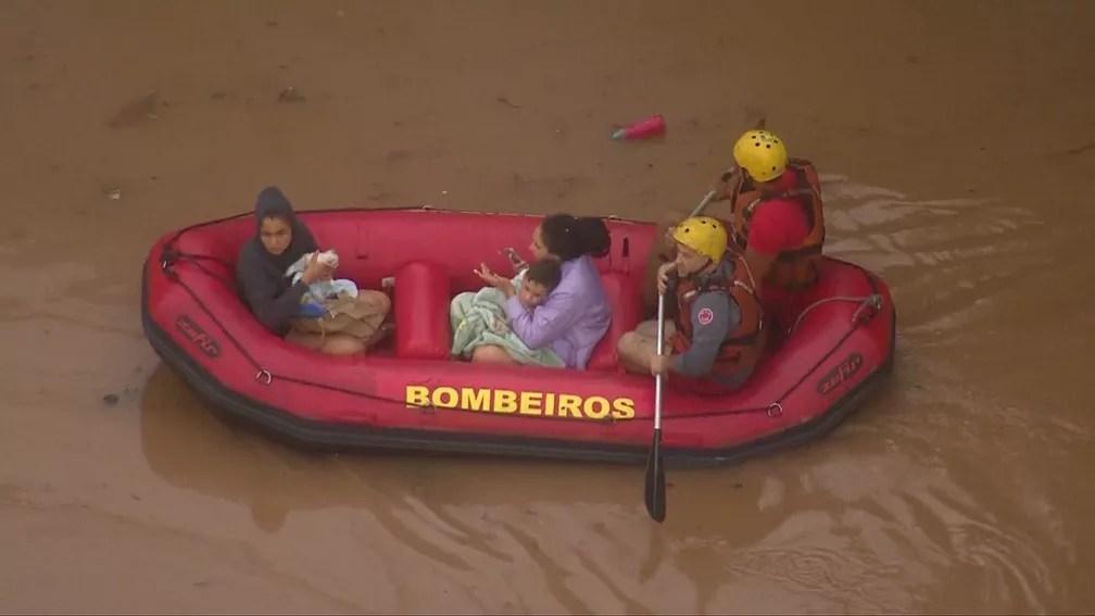 Criança é resgatada por bombeiros por bote em alagamento em São Paulo — Foto: Reprodução/TV Globo