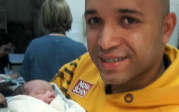 Samuel Ferreira Dias segura recém-nascido que localizou abandonado em banco de praça (Foto: Samuel Ferreira Dias/Arquivo Pessoal)