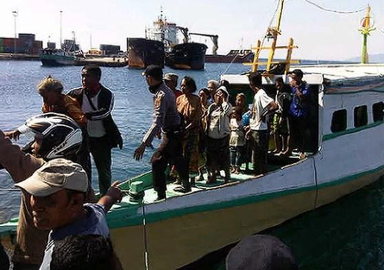 Moradores retirados da ilha de Palue chegam ao porto de Maumere neste domingo (11) (Foto: AFP)