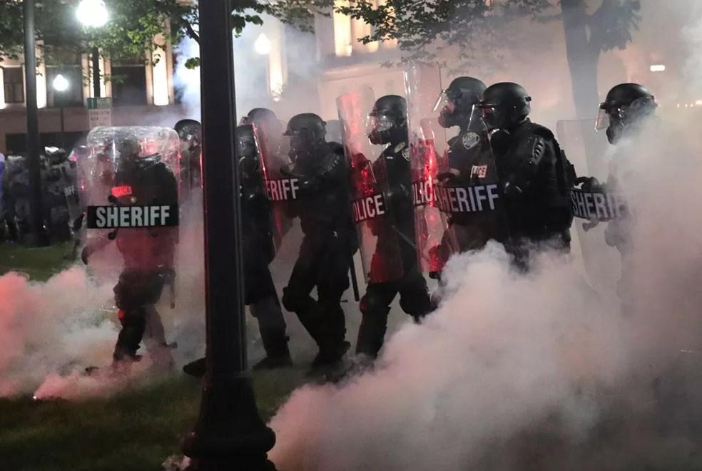 Polícia caminha enquanto gás lacrimogêneo se dispersa durante protesto perto do Tribunal de Kenosha, em Wisconsin, nos EUA , na madrugada desta quarta-feira (26)  — Foto: Scott Olson / Getty Images / AFP