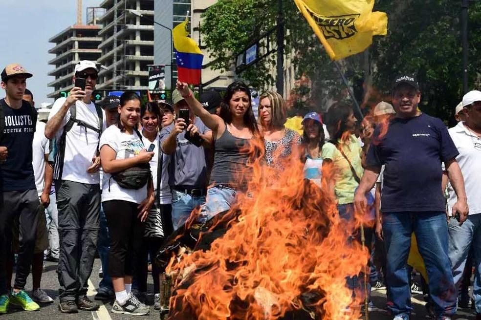 Manifestantes queimam foto do presidente da Venezuela, Nicolás Maduro,  durante protesto em Caracas (Foto: Ronaldo Schemidt / AFP)