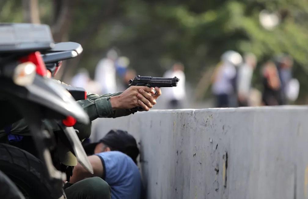 Um militar aponta uma arma perto da base aérea Generalisimo Francisco de Miranda, conhecida como 'La Carlota', em Caracas — Foto: Manaure Quintero/Reuters