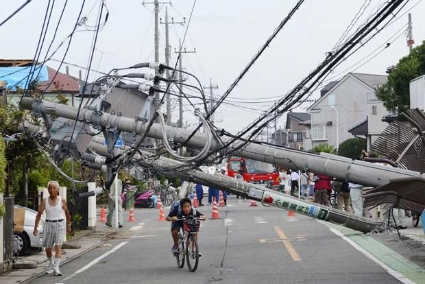 Garoto anda de bicicleta em meio à destruição em Koshigaya nesta segunda-feira (2) (Foto: Kyodo/AP)