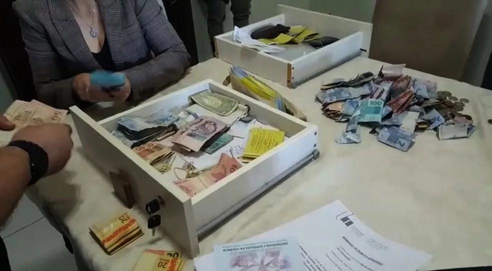Dinheiro apreendido em fundo falso do guarda-roupa do vigário-geral de Formosa, em Goiás, durante Operação Caifás (Foto: TV Anhanguera/Reprodução)