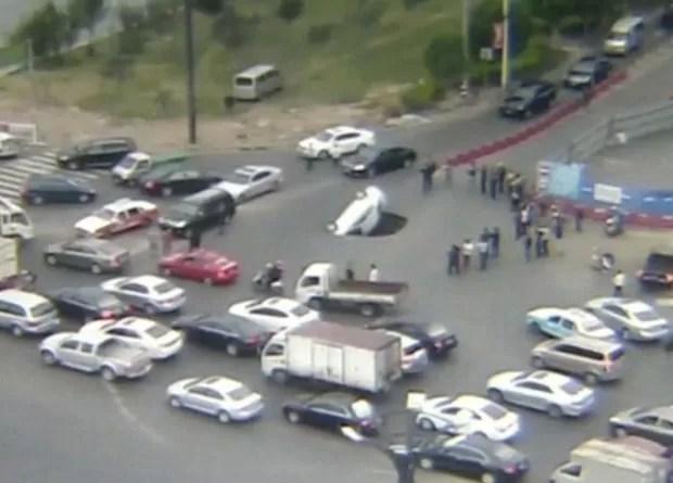 Motorista e passageiro conseguiram escapar antes de carro ser engolido por buraco na China (Foto: BBC)
