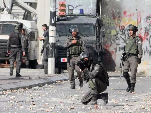 Soldados israelenses apontam armas contra palestinos nesta terça-feira (6) em Belém (Foto: AFP PHOTO / MUSA AL-SHAER)