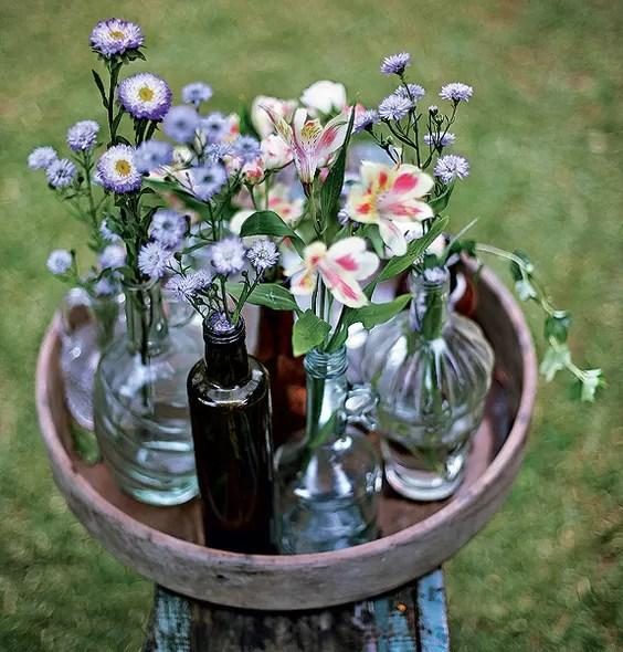 Nada de furos, fios ou quebra-quebra. Para montar este centro de mesa, basta reunir garrafas de diferentes cores e formatos e organizá-las em uma bandeja de madeira. Colha algumas flores no jardim e pronto!