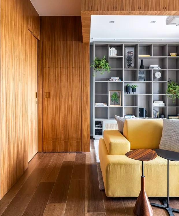 Living | Painéis e portas de madeira ajudam a organizar a distribuição de espaços no apartamento integrado (Foto: Renato Navarro/Divulgação)