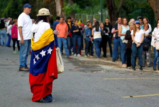 Venezuelanos fazem fila para votar no plebiscito contra o presidente Nicolás Maduro, neste domingo (16), em Caracas (Foto: Christian Veron/ Reuters)