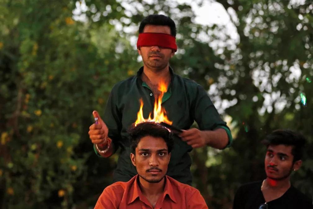 31 de maio - Vishnu Limbachiya, cabeleireiro, estiliza o cabelo de um homem enquanto veste uma venda em um parque em Ahmedabad, Índia (Foto: Amit Dave/Reuters)