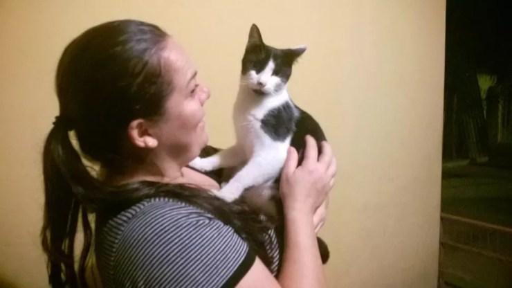 Protetora Katiusca Angelica Lopes com um dos 53 gatos que cuida (Foto: Francine Galdino/G1)