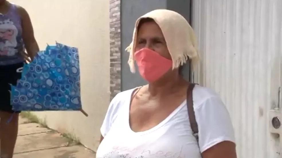 Beneficiários improvisam para se proteger do sol  — Foto: TV Clube