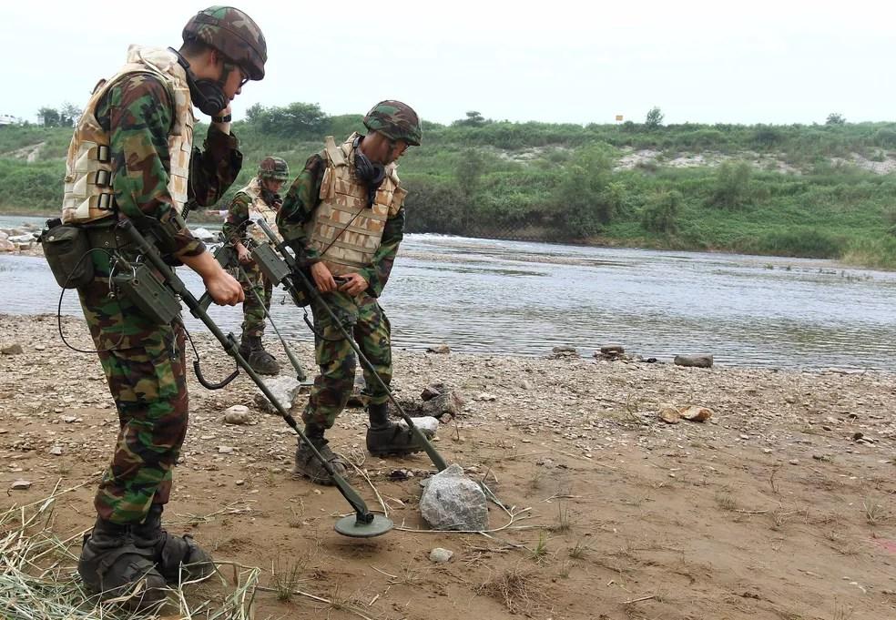Imagem de agosto de 2010 mostra soldados da Coreia do Sul procurando minas na área desmilitarizada que separa as duas Coreias — Foto: Lim Byung-shick/Yonhap via AP, File