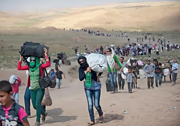 3. Sírios cruzam a fronteira com o Iraque, rumo aos campos de refugiados ao norte do país vizinho (Foto: Lynsey Addario/The New York Times)