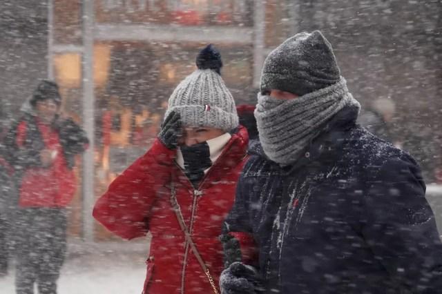 Pessoas enfrentam neve ao andar pela Times Square nesta quinta-feira (4) em Nova York (Foto: Carlo Allegri/Reuters)