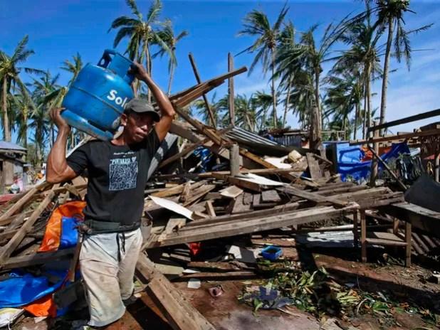 Vítima de tufão passa por casas destruídas carregando um tanque de gás para cozinhar na cidade Borongan , Samar, no centro das Filipinas (Foto: Reuters)