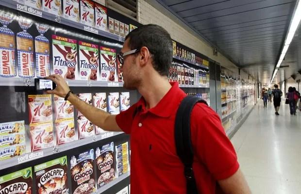 Homem faz compras usando o celular em estação de metrô de Barcelona (Foto: Gustau Nacarino/Reuters)