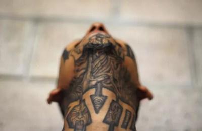 Membro da gangue Mara 18 tatuou imagem de demônio no pescoço (Foto: Ulises Rodriguez/Reuters)