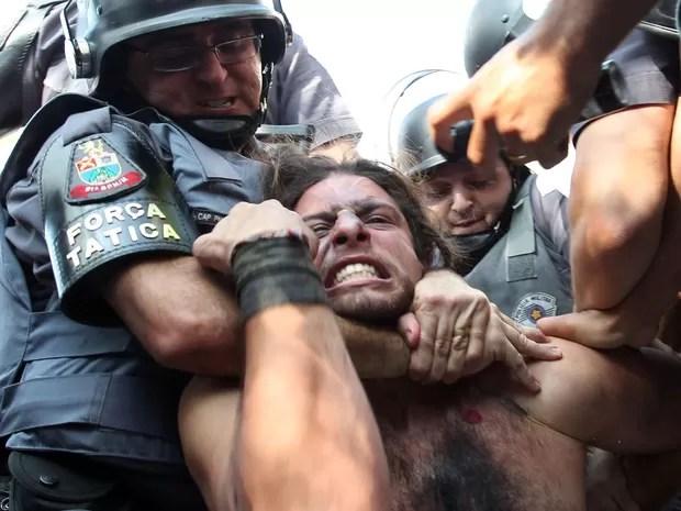Manifestante é detido pela polícia durante um protesto que tentou bloquear na Radial Leste, nos aredores da Estação Carrão da Linha 3-Vermelha do Metrô de São Paulo na manhã desta quinta-feira (12)