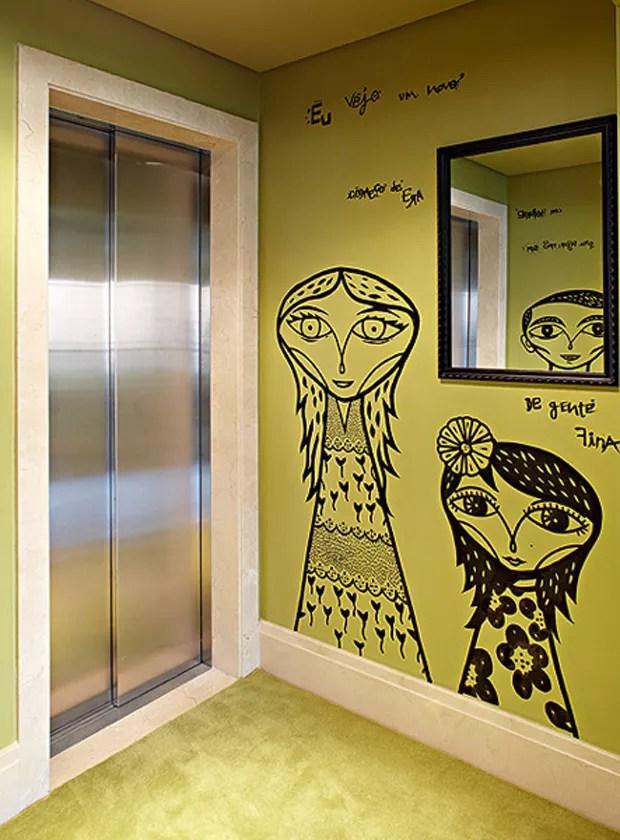 Para imprimir no apê a personalidade dos donos, a arquiteta Bruna Riscali tomou como referências arte urbana e fotografia. No hall de entrada do elevador, a parede recebeu caricaturas da própria família, grafitadas pelo artista Bruno Dias (Foto: Victor Affaro)
