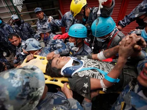 Jovem Pemba Lama é resgatado pelas equipes do Nepal e dos Estados Unidos após ficar soterrado por 5 dias sob os escombros de prédio que desabou durante terremoto na capital Katmandu (Foto: AP/Niranjan Shresta)