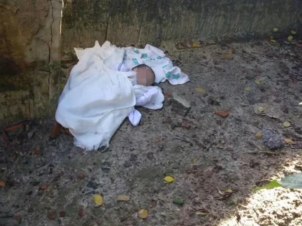 Bebê foi encontrado em terreno baldio após moradores se guiarem por latidos de cão (Foto: Polícia Militar/Divulgação)