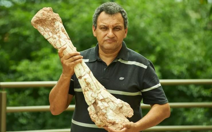 O auxiliar de paleontologia Cledinei Aparecido Francisco mostra fêmur de dinossauro em Monte Alto, SP — Foto: Érico Andrade/G1