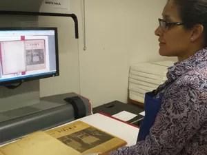 Coordenadora da Divisão de Coleções Especiais da Biblioteca da UFMG, Diná Araújo, demonstra como o Binõmio foi digitalizado (Foto: Thais Pimentel/G1)