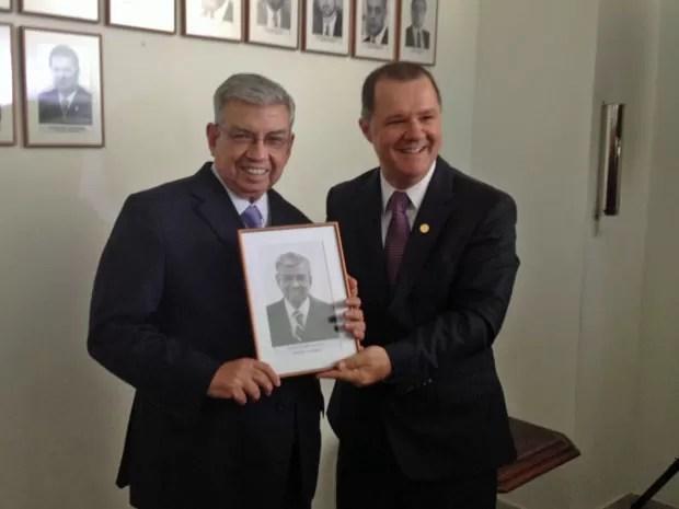 Os ministros Garibaldi Alves (esq.) e Carlos Gabas posam com quadro do primeiro, que irá para a galeria dos ministros (Foto: Fernanda Calgaro/G1)