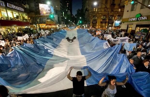 Manifestantes seguram bandeira argentina durante marcha contra governo da presidente Cristina Kirchner (Foto: Victor R. Caivano/AP)