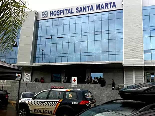 Fachada do Hospital Santa Marta, em Taguatinga, com carro da PM e policiais na entrada (Foto: Lucas Salomão/G1)