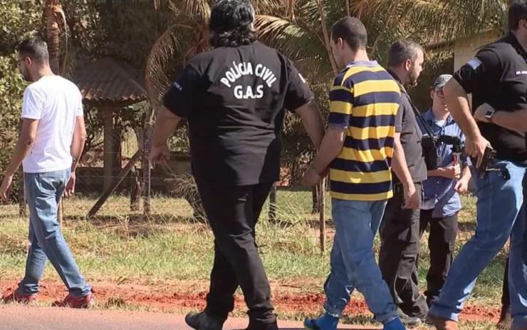 Policial leva um dos suspeitos durante a reconstituição do crime (Foto: Reprodução/ TV TEM)