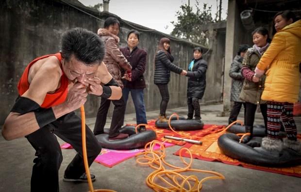 Nie Yongbing faz esforço para encher pneus com pessoas em cima usando o nariz, durante uma performance realizada em sua casa na China (Foto: Stringer/Reuters)