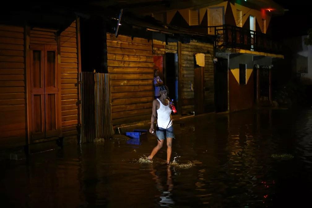Mulher atravessa uma rua inundada em Puerto Plata, República Dominicana (Foto: Ivan Alvarado/Reuters)