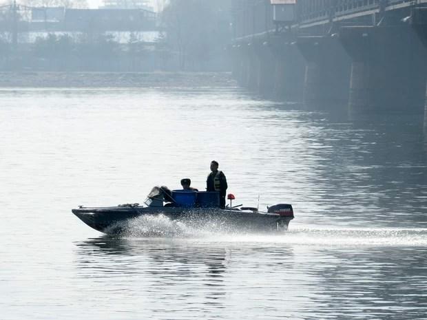 Patrulha norte-coreana cruza o rio Yalu entre Sinuiju, na Coreia do Norte, e Dandong, na China nesta quarta-feira (10). (Foto: Wang Zhao / AFP)