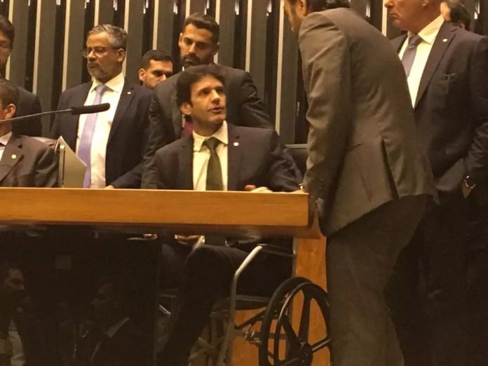 O ministro do Turismo, Marcelo Álvaro Antônio, ao tomar posse como deputado em cadeira de rodas — Foto: Fernanda Vivas / TV Globo