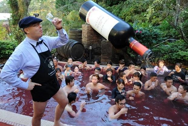 Vice-presidente da Laboure-Roi, Thibault Garin, brinda com convidados em piscina de vinho no Japão (Foto: Toshifumi Kitamura/AFP)