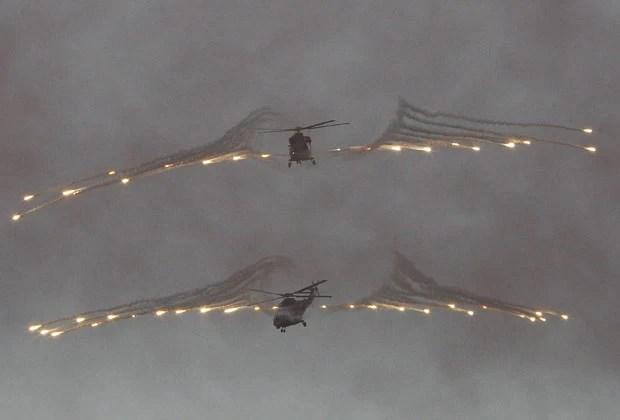 Novos helicópteros sul-coreanos fazem disparos durante apresentação nesta segunda (20) (Foto: Ahn Young-joon/AP)