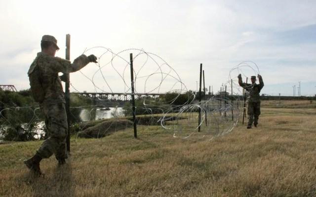 Soldados do 19º Batalhão de Engenharia de Kentucky instalam cercas de arame farpado nas margens do Rio Grande, em Laredo, no Texas, no domingo (18) — Foto: Thomas Watkins/AFP