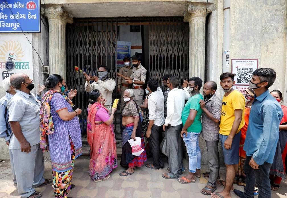 Policiais informam população sobre a falta de vacina contra a Covid-19 no portão de um centro de imunização em Ahmedabad, na Índia, em 29 de junho de 2021 — Foto: Amit Dave/Reuters