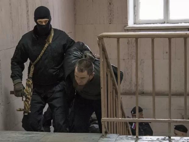 Em tribunal de Moscou, policial conduz neste domingo (8) um dos suspeitos do assassinato do opositor russo Boris Nemtsov (Foto: Ivan Sekretarev/AP)