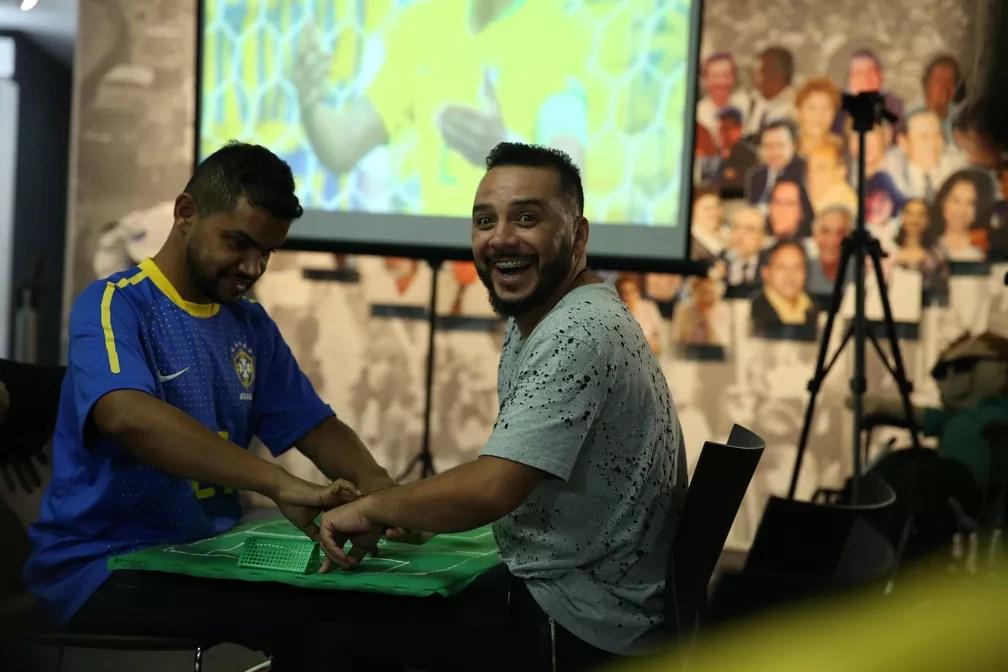 Carlinhos com camisa do Brasil e interprete Hélio acompanham o jogo da seleção (Foto: Marcelo Brandt/G1)