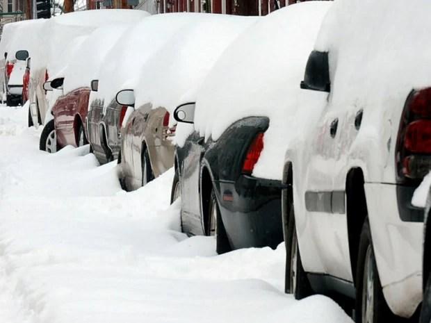 Morador de Washington retira neve; carros ficaram cobertos (Foto: AP)