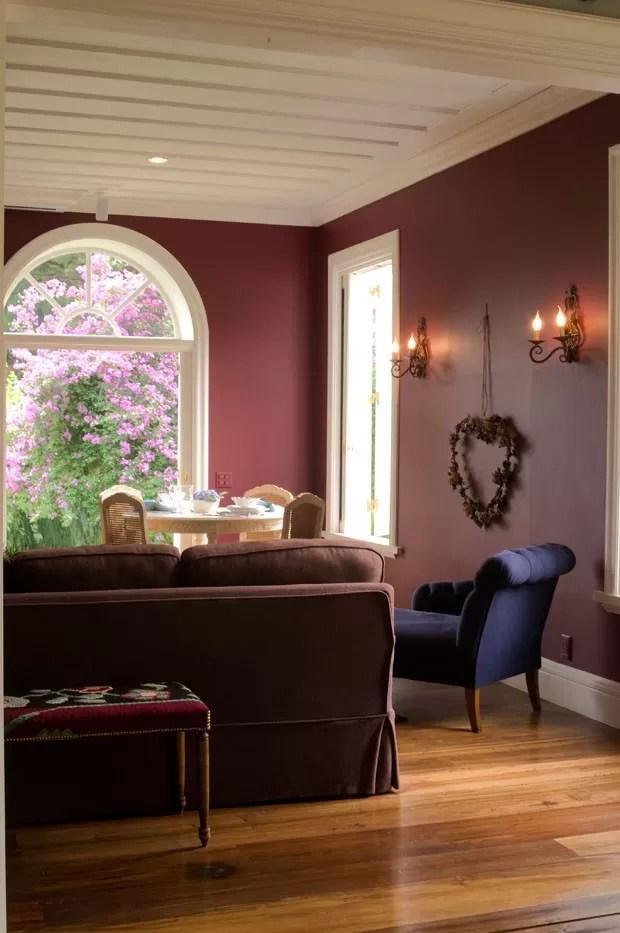 A sala ganhou um sofá feito sob medida para complementar os móveis da Secrets de Famille. Na parede foi aplicada tinta Suvinil, cor R109 (Foto: Divulgação)
